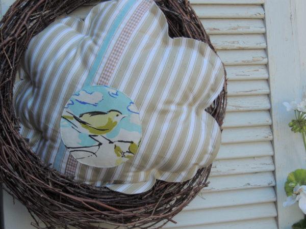 Joli Coussin en forme de fleur Une petite bergeronette dans les tons turquoise est accrochée Coussin 100% coton Coussin en toile à matelas Coussin lavable à 40° Coussin non déhoussable Dimension du coussin diam 40 cms
