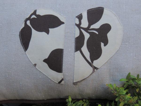 Coussin en lin et coton Coussin gansé d'un passepoil chocolat Coeur brisé appliqué sur le coussin en tissu à ramages marron Coussin déhoussable finition portefeuille Intérieur du coussin 100% polyester Dimensions du coussin 30 X 53 cms Coussin lavable à 40°