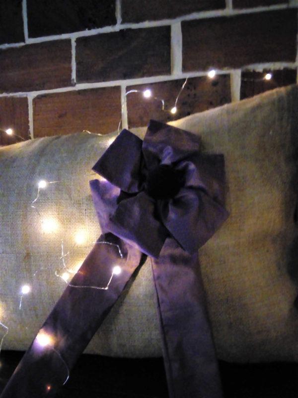 Grand coussin en toile de jute dimensions 90 cms X 52 cms Face arrière du coussin en taffetas violet Grosse cocarde en taffetas violet avec centre en velours Cocarde amovible avec pression Coussin déhoussable Intérieur du coussin 100% polyester Conseil de lavage 30°