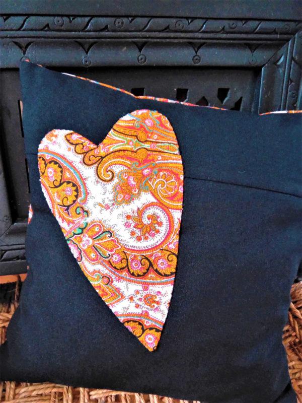 Coussin carré de dimensions 35 X 35 cms coussin noir avec un grand coeur appliqué dans les tons orange Matière du tissu polyester et coton Coussin déhoussable finition portefeuille Intérieur du coussin 100% polyester Conseil de lavage 40°