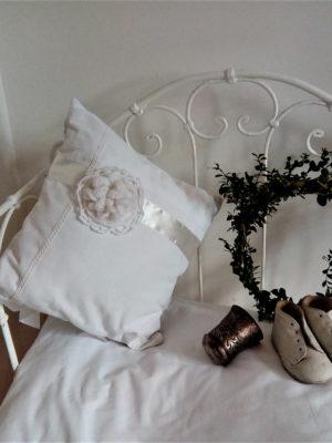 Coussin carré de dimensions 35 X 35 cms Coussin taillé dans un drap ancien blanc Coussin agrémenté de ruban satin blanc, d'une grande fleur crochetée main, et de dentelle Ce coussin est déhoussable, avec des noeuds de satin blanc pour la fermeture Matière du coussin 100% coton Intérieur du coussin 100% polyester Conseil de lavage 30°