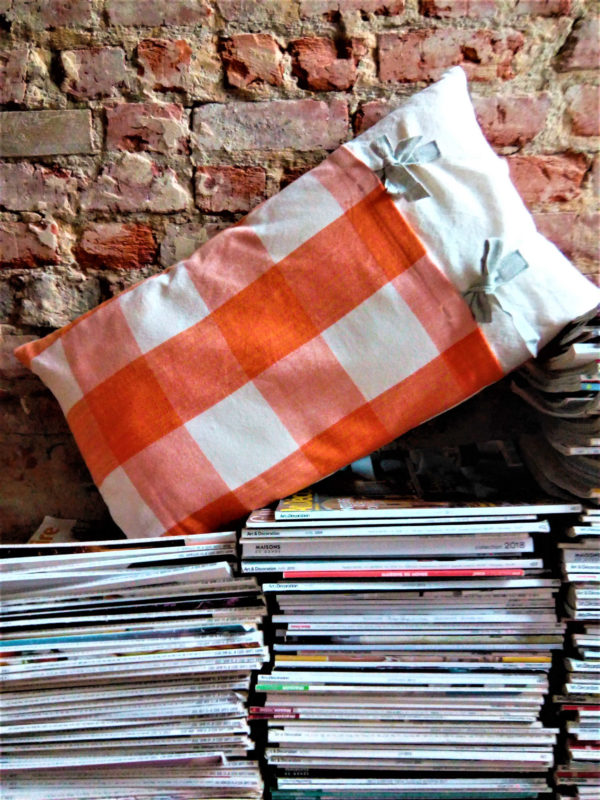 Coussin rectangulaire de dimensions 40 X 65 cms Coussin en tissu de gros carrés oranges Appliqué d'un tissu fond blanc avec des fleurs roses, vertes et oranges Des rubans de coton gris, vert et orange sont cousus La face arrière du coussin est en tissu à carrés oranges également Coussin déhoussable finition portefeuille avec deux noeuds en ganse de coton grises Tissu 100% coton Intérieur du coussin 100% polyester Conseil de lavage 40°