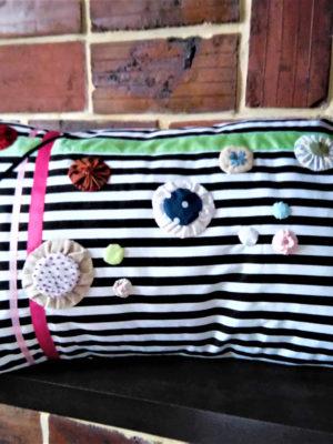 Coussin rectangulaire dimensions 35 cms X 58 cms tissu rayé noir et blanc Coussin agrémenté de rubans roses et verts Coussin parsemés de yoyos de différentes couleurs, certains rebrodés Coussin 100% coton Coussin déhoussable finition portefeuille Conseil de lavage 40°