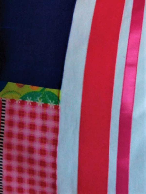 Coussin carré de dimensions 40 X 40 cms La moitié du coussin est de soie sauvage bleu marine assortie à un tissu fantaisie dans les tons rouges, roses et verts L'autre moitié d'un coton blanc agrémenté de deux rubans de satin rouge et rose La face arrière du coussin est blanche Coussin déhoussable finition portefeuille Intérieur du coussin 100% polyester Conseil de lavage 30°