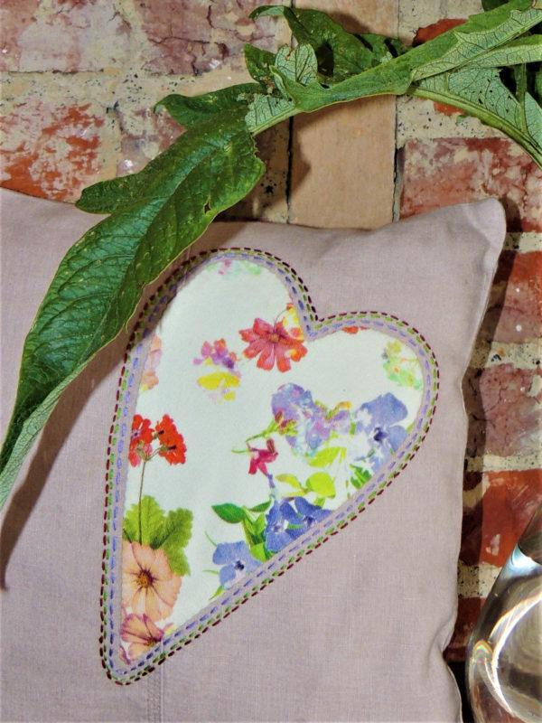 Coussin carré de dimensions 35 X 35 cms Coussin en lin avec un coeur appliqué dans un tissu fleuri aux tons vifs Le coeur est surligné d'une piqure main Matière du tissu, coton et lin Coussin déhoussable finition portefeuille Intérieur du coussin 100% polyester Conseil de lavage 40°