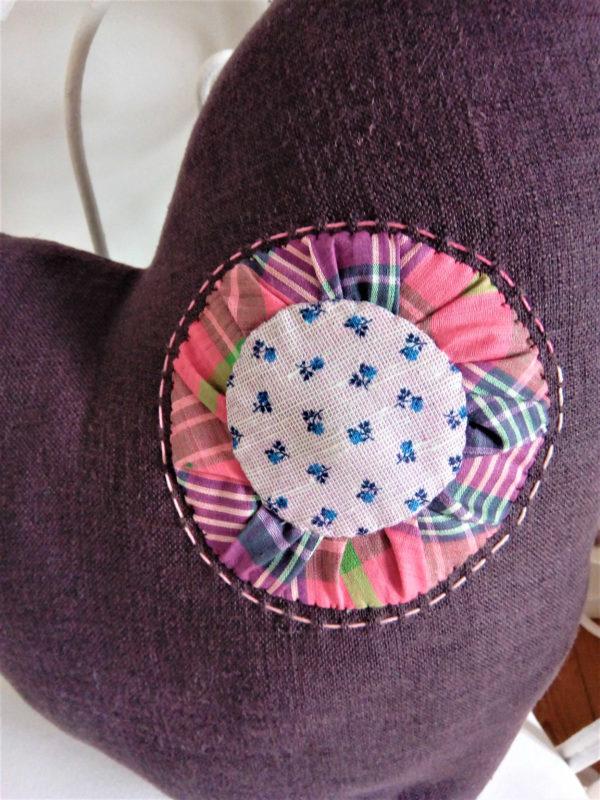 Coussin en forme de coeur Coussin en tissu couleur prune avec un yoyo cousu dans les tons roses Coussin non déhoussable Coussin 100% coton Dimensions du coussin 40 X 40. cms Intérieur du coussin 100% polyester Conseil de lavage à 40°