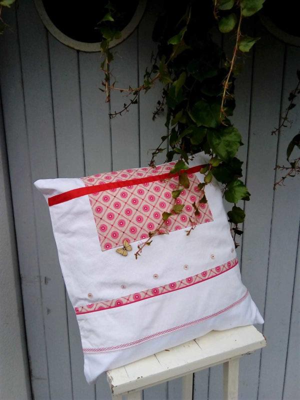 Coussin carré 40 X 40 cms Fond blanc et tissu fantaisie dans les tons roses fushia, ruban de satin rouge Petits boutons blancs et bouton papillon en bois Coussin 100% coton Coussin déhoussable finition portefeuille Intérieur du coussin 100 % polyester Conseil de lavage 40°