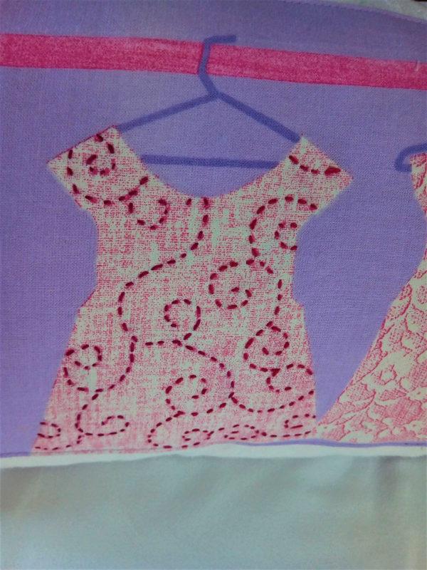 Petit coussin rectangulaire dimensions 25 cms X 50 cms Coussin ton mauve agrémenté de 3 petites robes dans les tons roses Petits boutons cousus, et petite robe rebrodée Tissu du coussin 100% coton Coussin non déhoussable Intérieur du coussin 100% polyester Conseil de lavage 30°