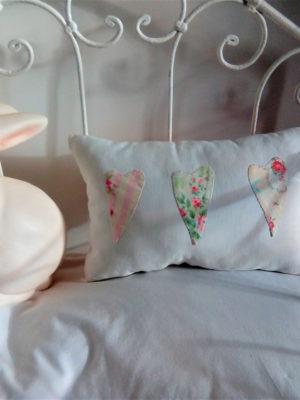 Petit coussin rectangulaire blanc dimensions 24 cms X 36 cms 3 petits coeurs en tissu fantaisie sont appliqués sur le coussin à tous petits points Les petits coeurs sont dans les tons roses et verts coussin 100% coton Ce coussin n'est pas déhoussable le dos du coussin est rose pâle avec un petit coeur beige brodé main L'intérieur du coussin est 100% polyester Conseil de lavage à 30°