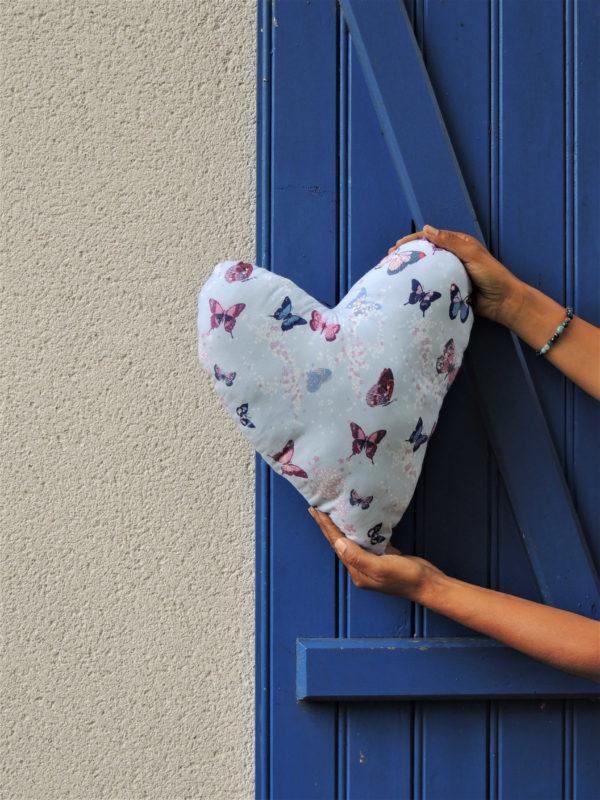 Coussin dans les tons bleus avec de jolis papillons Coussin en forme de coeur Dimensions du coussin 34 cms X 40 cms Le tissu de ce coussin est 100% coton L'intérieur de ce coussin est 100% polyester