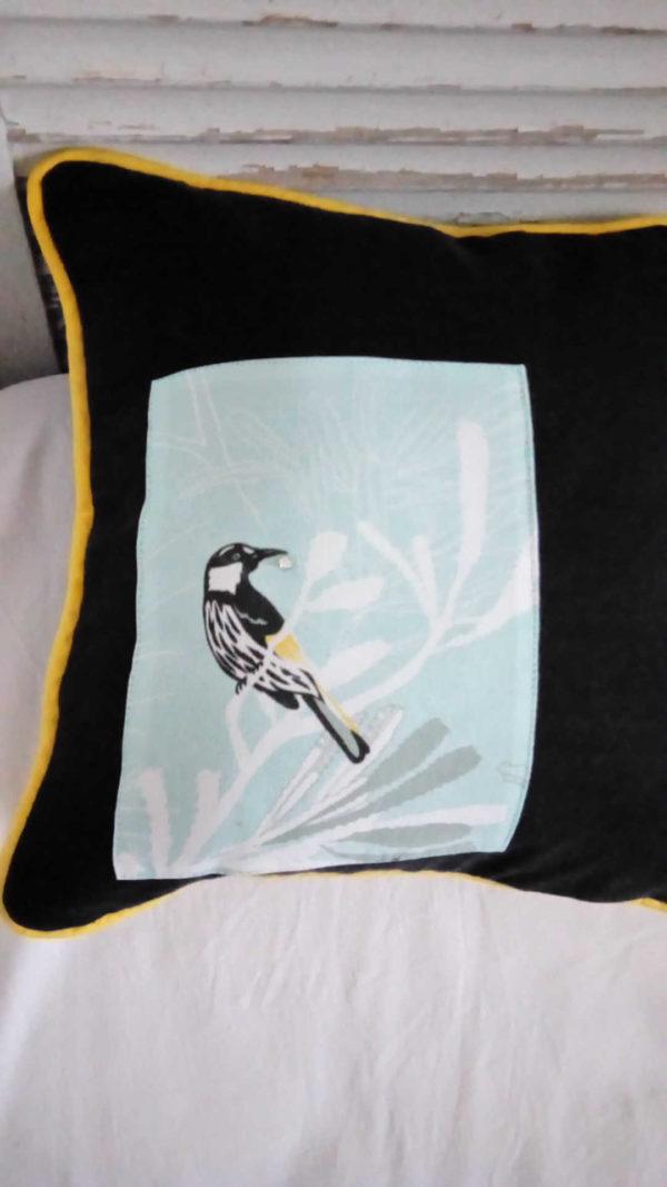 coussin carré de taille 38 cms par 38 cms fond noir et appliqué d'un joli tissu turquoise pâle coussin gansé de jaune une pie a un strass dans son bec . coussin 100% coton déhoussable. L'envers du coussin est noir et jaune avec des petits boutons jaunes