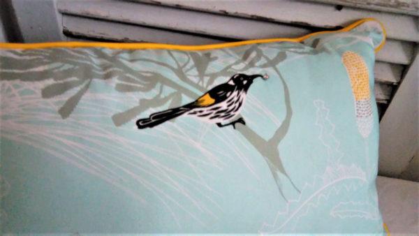coussin de dimensions 60 cms par 32 cms dans un joli tissu turquoise pâle. des pies sont posées sur ce coussin et une d'elle a un strass dans son bec. La housse du coussin est 100% coton et l'intérieur du coussin est 100% polyester. Le coussin est gansé de jaune et n'est pas déhoussable. L'envers du coussin est noir.