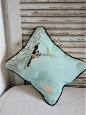 petit coussin de dimensions 28 cms par 34 cms, dans un joli tissu turquoise pâle, coussin gansé d'un passepoil noir, . Une pie sur le coussin a volé un strass dans les boîtes de perles de l'atelier. L'extérieur du coussin est 100% coton et l'intérieur du coussin est 100% polyester. L'envers du cusssin est jaune et ce coussin est déhoussable