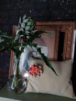 coussin en lainage dans un joli ton de vert, agrémenté d'une fleur au crochet faite main dans des tons verts et orangés parfaitement assortie au coussin. coussin de dimensions 33 cms par 40 cms, déhoussable finition portefeuille