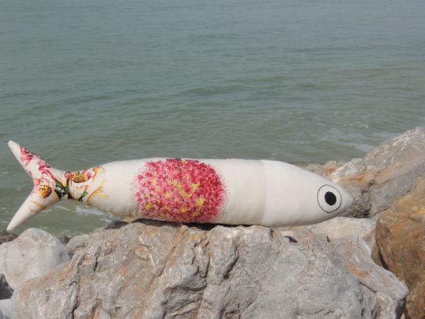 coussin en forme de poisson, longueur du coussin 72 cms, hauteur du coussin 17 cms, en tissu d'ameublement recyclé. Tissu très coloré avec de grosses fleurs roses et jaunes sur fond blanc