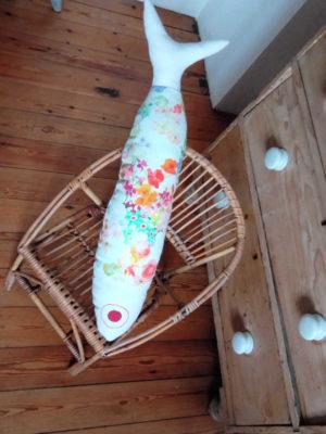 coussin en forme de grand poisson en tissu recyclé , fleurs de couleurs vives sur un fond blanc, longueur du coussin 72 cms, largeur du coussin 17 cms