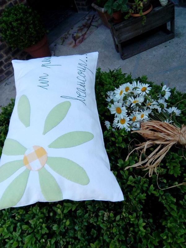 coussin rectangulaire dimensions 30 cms par 50 cms, en tissu recyclé, grosse marguerite verte appliquée sur un coussin blanc, les mots un peu , beaucoup sont brodés main , coussin déhoussable finition portefeuille.